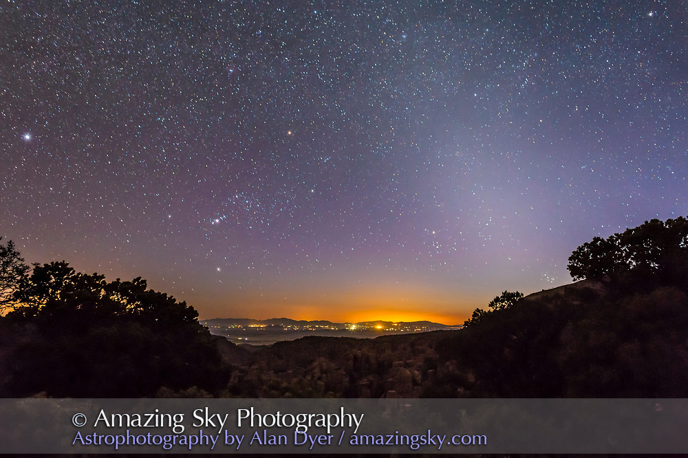 The northern winter constellations setting in the west and the Zodiacal Light in the western evening sky, shot from Chiricahua National Monument, at Massai Point, 6800 feet, in southeastern Arizona, April 29, 2014. Orion is setting at left of centre, and Sirius is at the left edge. The Pleiades are just going down behind the ridge at right, while Aldebaran and the Hyades sit amid the spring evening Zodiacal Light. I shot this as part of a 300-frame day-to-night time-lapse sequence using the Canon 6D and 24mm lens. This is a 30-second exposure at f/4 and ISO 3200.