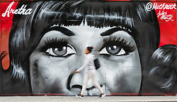 August 19, 2018 - London, England: A woman walks past new street art in Shoreditch, east London, paying tribute to the singer, Aretha Franklin who has died following a battle with pancreatic cancer.  The mural has been created by artist, Jules Muck in collaboration with Global Street Art. (Credit Image: © Vickie Flores/London News Pictures via ZUMA Wire)