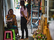 30 JULY 2016 - BANGKOK, THAILAND: Women chat in an alley in the Pom Makahan Fort slum. Residents of the slum have been told they must leave the fort and that their community will be torn down. Mahakan Fort was built in 1783 during the reign of Siamese King Rama I. It was one of 14 fortresses designed to protect Bangkok from foreign invaders. Only of two are remaining, the others have been torn down. A community developed in the fort when people started building houses and moving into it during the reign of King Rama V (1868-1910). The land was expropriated by Bangkok city government in 1992, but the people living in the fort refused to move. In 2004 courts ruled against the residents and said the city could take the land. Eviction notices have been posted in the community and people given until April 30 to leave, but most residents have refused to move. Residents think Bangkok city officials will start evictions around August 15, but there has not been any official word from the city.      PHOTO BY JACK KURTZ