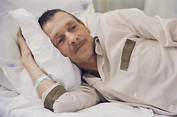 Patient lying in bed on hospital ward,