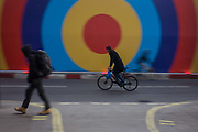 A cyclist and pedestrian pass-by in a London street with circles on a construction hoarding behind. Purposely blurred as they pass across this urban scene, we see the figures in the same posture, back bent and leaning forward towards their destinations. Concentric circles on the background hoarding belongs to a new business due to open soon on this bust shopping street in central London.