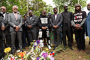 Rev. Al Sharpton and civil rights activists stand for a prayer during a peace vigil at the spot where unarmed motorist Walter Scott was gunned down by police April 12, 2015 in North Charleston, South Carolina. About 100 people showed up for the brief vigil following a healing service at Charity Mission Baptist Church.