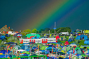 The rains return forcing people to shelter inany available space and  leading to mud and rainbows over a tent designed like an underground carriage. The 2014 Glastonbury Festival, Worthy Farm, Glastonbury. 27 June 2013.  Guy Bell, 07771 786236, guy@gbphotos.com