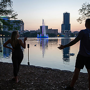 A couple jokes around about social distancing at Lake Eola Park on Friday, March 27, 2020 in Orlando, Florida.  (Alex Menendez via AP)