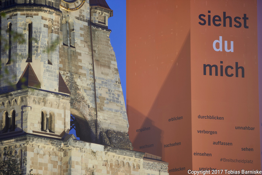 """The bell tower (right) of the Kaiser Wilhelm Memorial Church (left) is covered with a special version of the motto """"Du siehst mich"""" to advertise for the upcoming german protestant church congress in Berlin."""