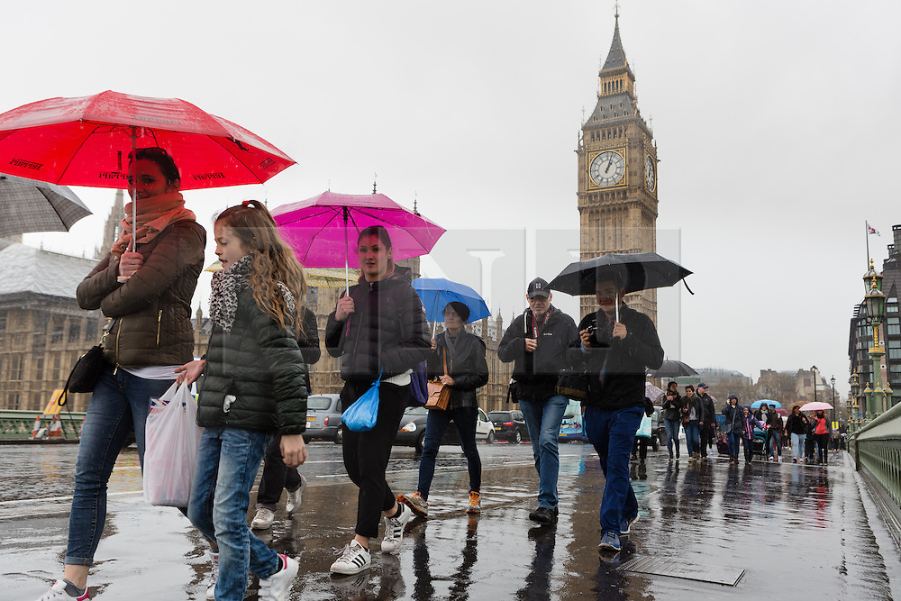 © Licensed to London News Pictures. 15/04/2016. London, UK. Tourists are caught in heavy rain showers near Big Ben in central London during wet and windy weather today. Photo credit : Vickie Flores/LNP