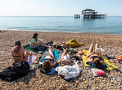 "© Licensed to London News Pictures. 14/09/2020. Sussex, UK. A group of six sunbathers enjoy the hot sunshine this afternoon on Brighton Beach while keeping to the ""Rule of Six"" as a mini-heatwave hits England this week with highs of 29c. Prime Minister Boris Johnson announced last week that gatherings of more than six people will be banned from today in the hope of reducing the coronavirus R number. The Rule of Six as it is known, has already become unpopular with MPs and large families for being too strict. Photo credit: Alex Lentati/LNP"