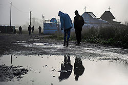 © Licensed to London News Pictures. 23/10/2016. Calais, France. Two young migrants walk in front of the church at the camp, act sunrise. Daily life continues as preparations begin for the demolition of the migrant camp in Calais, France, known as the 'Jungle'. French authorities have given an eviction order to thousands of refugees and migrants living at the makeshift living area of the French coast. Photo credit: Ben Cawthra/LNP