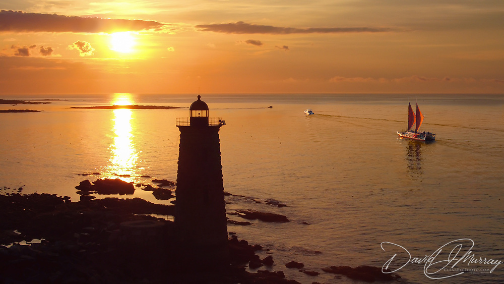 The Polynesian doube-hulled voyaging canoe Hōkūleʻa sails north past Whaleback light house off Kittery ME at dawn on July 19, 2016, on its way to Portland, ME, next stop on its world wide voyage.