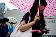 People with umbrellas in the city center of the Korean metrolpolis Seoul.