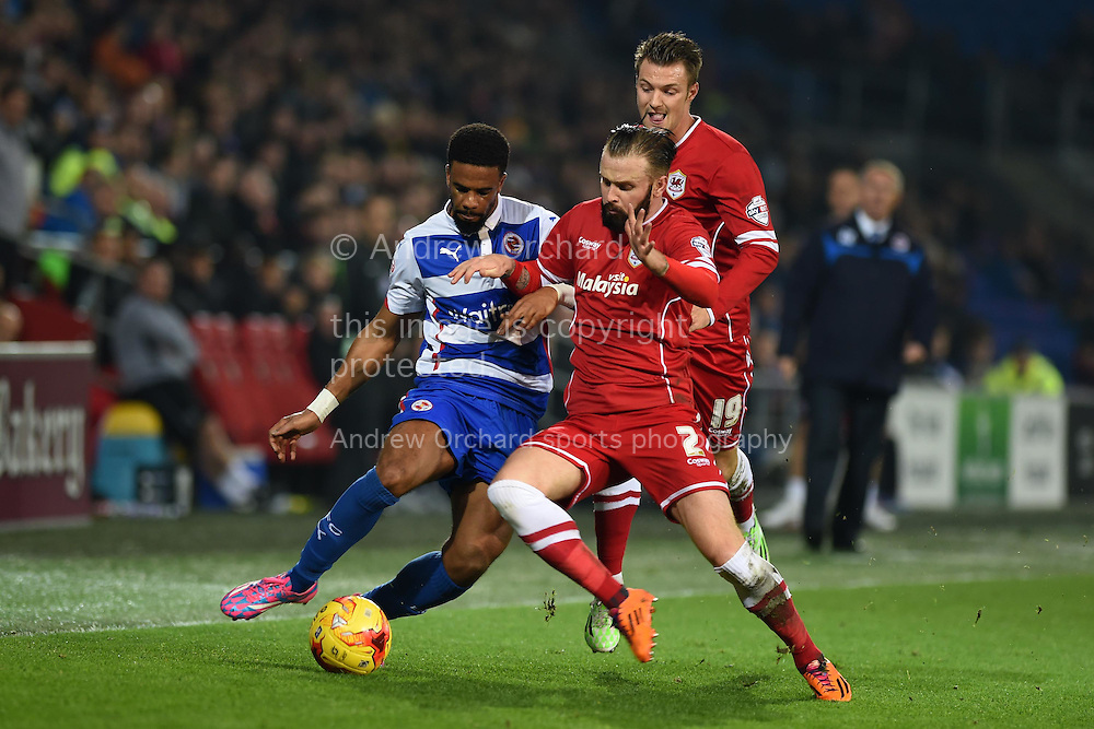 Gareth McCleary of Reading (l) looks to go past Cardiff's John Brayford ® and Anthony Pilkington (c) .Skybet football league championship match, Cardiff city v Reading at the Cardiff city stadium in Cardiff, South Wales on Friday 21st November 2014<br /> pic by Andrew Orchard, Andrew Orchard sports photography.