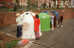 Multiracial group of young children recycling glass,