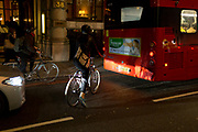 A waiting cyclist is illuminated by car headlights behind a London bus in the Square Mile, the heart of the capital's historical financial district, on 2nd October 2017, in the City of London, England.