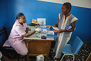 A midwife hands her prescription and health carnet to Keukeu Laito, 29, who is 5-month pregnant with her second child, during a prenatal consultation at the Libreville health center in Man, Cote d'Ivoire on Wednesday July 24, 2013.