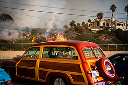 November 9, 2018 - Malibu, California, U.S. - A vintage car sits in a parking lot off Pacific Coast Highway as flames from the Woolsey Fire back up a nearby hillside.  The Woolsey Fire in Malibu Friday. The Santa Ana Wind driven fire destroyed homes and was burning near the Pacific Ocean. (Credit Image: © Stuart Palley/ZUMA Wire/ZUMAPRESS.com)