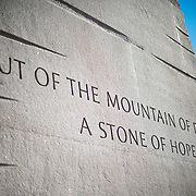 """An inscription on the side of the base of the statue of civil rights leader Dr Martin Luther King Jr emerging out of the Stone of Hope that forms the centerpiece of the MLK Memorial on the banks of the Tidal Basin in Washington DC. The sculpture was created by Chinese sculptor Lei Yixin. The inscription reads: """"Out of the mountain of despair a stone of hope."""""""