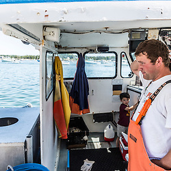 Captain Johnny McCarthy (right), his son Jack aboard the 'Isabella - Jack' at the Vinalhaven Fishermen's Co-op in Vinalhaven, Maine.