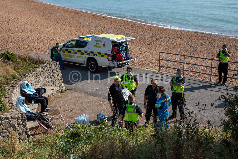 HM Coast Guard staff and local police help asylum seekers who have spent all night travelling by dinghy from France to the UK, landing on the beach in Folkestone, United Kingdom on the 8th of October 2021. There were 13 people who crossed the busy shipping channel over night, all wearing life jackets. They were cold and dehydrated when they landed.
