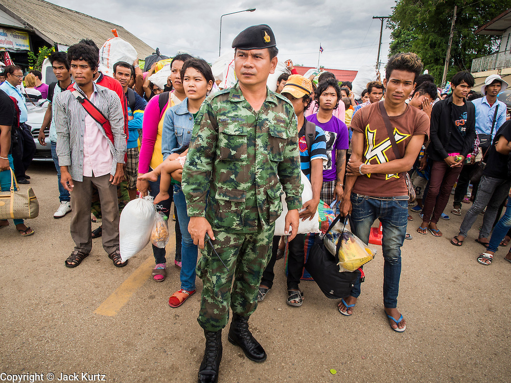16 JUNE 2014 - ARANYAPRATHET, THAILAND: A Thai army officer waits to walk a group of Cambodian migrants through Aranyaprathet, Thailand to the immigration police station. More than 150,000 Cambodian migrant workers and their families have left Thailand since June 12. The exodus started when rumors circulated in the Cambodian migrant community that the Thai junta was going to crack down on undocumented workers. About 40,000 Cambodians were expected to return to Cambodia today. The mass exodus has stressed resources on both sides of the Thai/Cambodian border. The Cambodian town of Poipet has been over run with returning migrants. On the Thai side, in Aranyaprathet, the bus and train station has been flooded with Cambodians taking all of their possessions back to Cambodia. PHOTO BY JACK KURTZ