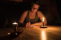 Female hiker writes in journal by candlelight at Abiskojaure hut, Kungsleden trail, Lapland, Sweden