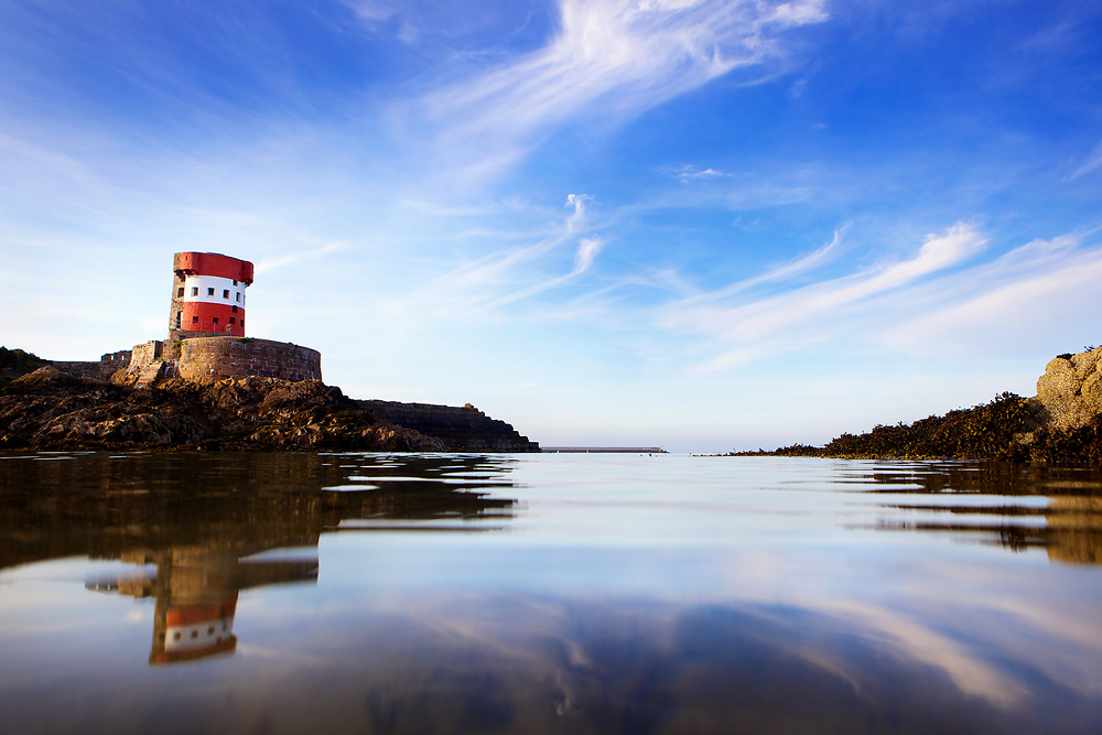Archirondel Tower and sky reflecting in the glassy calm water at Archirondel beach on the east coast of Jersey, C.I.