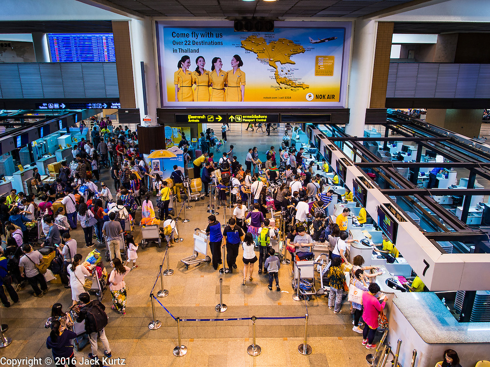 """23 FEBRUARY 2016 - BANGKOK, THAILAND:  Passengers in line to check for international flights on Nok Air at Don Mueang International Airport. Nok Air, partly owned by Thai Airways International and one of the largest and most successful budget airlines in Thailand, cancelled 20 flights Tuesday because of a shortage of pilots and announced that other flights would be cancelled or suspended through the weekend. The cancellations came after a wildcat strike by several pilots Sunday night cancelled flights and stranded more than a thousand travelers. The pilot shortage at Nok comes at a time when the Thai aviation industry is facing more scrutiny for maintenance and training of air and ground crews, record keeping, and the condition of Suvarnabhumi Airport, which although less than 10 years old is already over capacity, and facing maintenance issues related to runways and taxiways, some of which have developed cracks. The United States' Federal Aviation Administration late last year downgraded Thailand to a """"category 2"""" rating, which means its civil aviation authority is deficient in one or more critical areas or that the country lacks laws and regulations needed to oversee airlines in line with international standards.        PHOTO BY JACK KURTZ"""