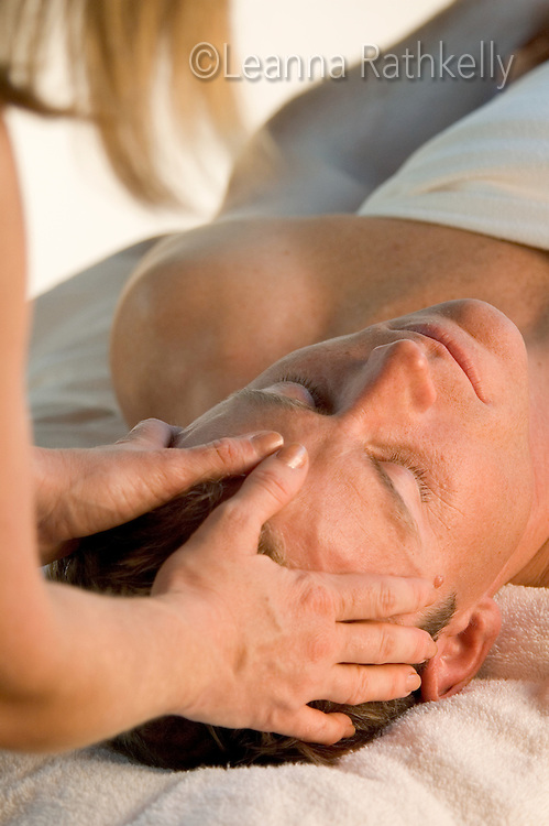 A man relaxes while he enjoys a head massage.