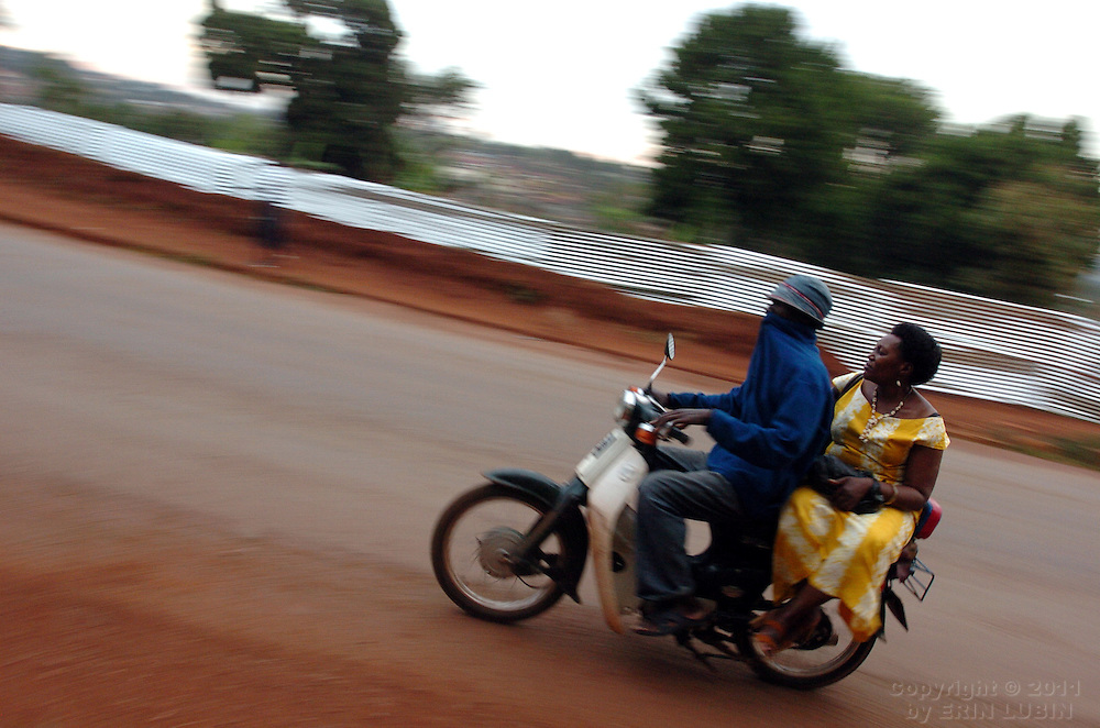 A woman catches a ride on a moped in Kampala, Uganda, October 1, 2006...Photo by Erin Lubin