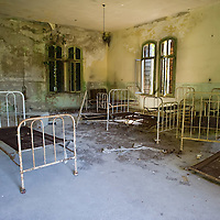 VENICE, ITALY - AUGUST 27:  Beds and furniture lie in one of the dormitories in the psychiatric ward of the abandoned Hospital of Poveglia on August 27, 2011 in Venice, Italy. The island of Poveglia, with its ruined hospital and plague burial grounds, is said to be the most haunted location in the world. Though it is a multi-million dollar piece of real estate it lies deserted and off limits to the public. Its dark, forbidding shores are only minutes away from the glamour of the Venice Film Festival on the Lido. ...To discuss licensing our 4000 word photo documentary of the island, email robin@robinsaikia.com. ..British author Robin Saikia visited the site with Italian photographer Marco Secchi. Marco captured the sinister atmosphere of the island. Robin describes the terrifying apparitions and the stories behind them.