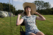 Seated in a camping chair, a 15 year-old teenage girl is happy in a field whilst on a family camping holiday. She is on a family holiday on the North Devon coast in southwest England and wears a floppy hat that is pulled down on her shoulders. In the background we see the guy ropes and poles from her family tent and also a neighbouring tent in the corner of this meadow belonging to a local farmer. The campsite is basic without crowds of caravanners and other noisy holidaymakers. The grass is lush and green suggesting it has been a wet summer.
