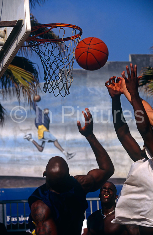 Although we see the arms and bodies of three young African American men jumping high for a basketball, there is a fourth arm trying to make contact with the ball as all four males leap high at the basket ball net which has just bounced off the ring, scoring no points. We see the face of one black man whose white teeth and silver-coloured necklace shine in the sunshine. He looks up to watch the other hands fight for the ball's possession as the teams battle for supremacy. In the background is a mural painted on the court's wall showing a running dribbling basket ball player who seems to be leaping over the head of one player in the foreground. There are large tattooed deltoid shoulder muscles and masses of energy on show in this scene of ultimate determination and desire to win.