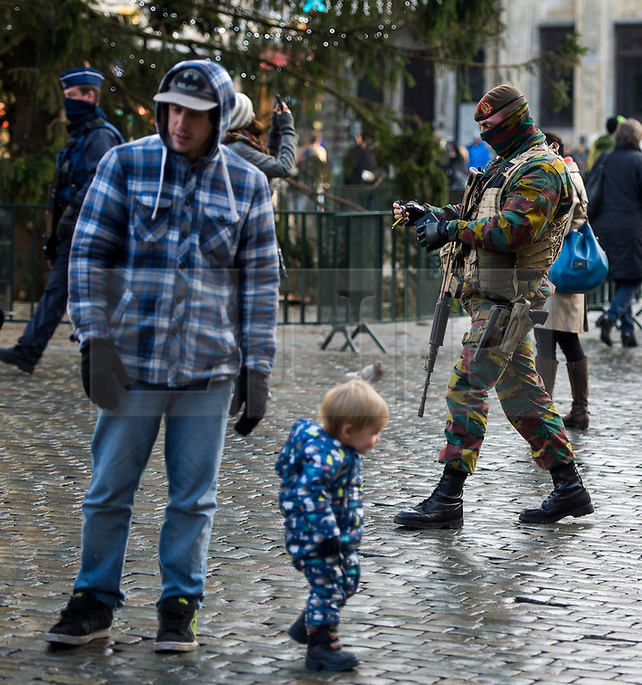 """© Licensed to London News Pictures. 23/11/2015. Brussels, Belgium. Belgian military patrolling past tourists in The Grand Place, the main square in central Brussels where the city is currently on lockdown amid """"imminent threat"""" of Paris-style bomb and gun attacks. Some public transport and schools have been closed as a precaution. Photo credit: Ben Cawthra/LNP"""