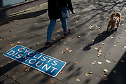 A pet dog walks along the Thames riverbank where cyclists are urged to dismount, on 7th November 2019, in Kingston, London, England.