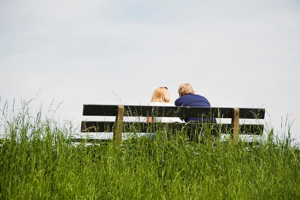 Nederland, Edam, 5 juli  2009.Man en vrouw op een bankje op een dijk aan het IJsselmeer voeren een goed gesprek, turend over het water...Foto (c) Michiel Wijnbergh..Man and woman on a bench at a dyke