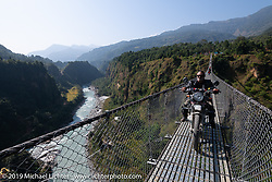 Cool Beans Chris Marino riding a Royal Enfield Himalayan crossing a long and very tall suspension bridge during Motorcycle Sherpa's Ride to the Heavens motorcycle adventure in the Himalayas of Nepal. On the sixth day of riding, we went from Tatopani to Pokhara. Saturday, November 9, 2019. Photography ©2019 Michael Lichter.
