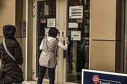 A woman cleans the entrance of a bank in Athens, Greece on March 23, 2020 as the country is battling hard to control the spread of the COVID-19, the novel coronavirus. Greek Prime Minister announced a ban on public movement starting at 06:00 am on March 23, 2020 to stem the spread of the global coronavirus pandemic in Greece.<br /> <br /> Pictured: <br /> Dimitris Lampropoulos  | EEm date