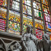 Statues of Mary in front of a colorful stained glass window at the Cathedral of St. Michael and St. Gudula (in French, Co-Cathédrale collégiale des Ss-Michel et Gudule). A church was founded on this site in the 11th century but the current building dates to the 13th to 15th centuries. The Roman Catholic cathedral is the venue for many state functions such as coronations, royal weddings, and state funerals. It has two patron saints, St Michael and St Gudula, both of whom are also the patron saints of Brussels.