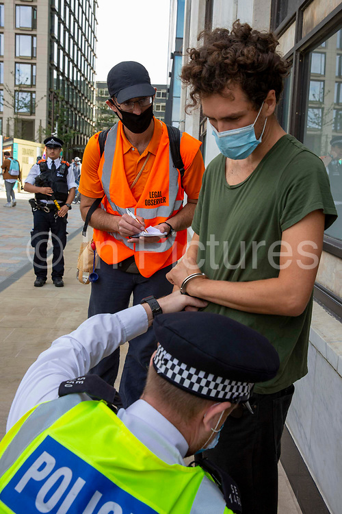 A legal observer keeps a close eye as police arrest a man who attempted to climb the Shell building as part of Extinction Rebellion 'Shell Out' protest on 8th September 2020 in London, United Kingdom. The environmental group gathered outside the Shell building to protest at the ongoing extraction of fossil fuels and the resulting environmental record. Extinction Rebellion is a climate change group started in 2018 and has gained a huge following of people committed to peaceful protests. These protests are highlighting that the government is not doing enough to avoid catastrophic climate change and to demand the government take radical action to save the planet.