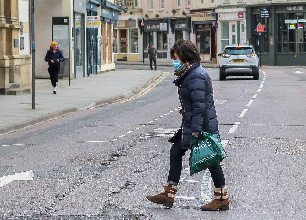 23rd February, Cheltenham, England. A shopper crosses the street wearing a mask in Cheltenham during the third national lockdown.