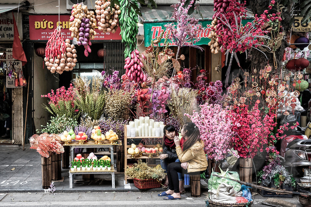 Young vendors chat while waiting for customers to buy Tet decorations from their stall along Hang Ma Street in Hanoi's Old Quarter, Vietnam, Southeast Asia