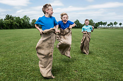 Three young boys running in sackrace jumping