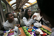Parker Smith, 15, and Erin James, 14, join others in playing games  on the train ride.