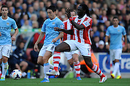 Manchester City's Samir Nasri battles with Stoke's Kenwyne Jones during the Barclays Premier league match, Stoke city v Manchester city at the Britannia Stadium in Stoke on Trent on Sat 14th Sept 2013. pic by Jeff Thomas, Andrew Orchard sports photography,