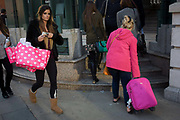 Women with matching coloured pink possessions in a City of London street. In a scene of pinks, a tall, elegant young woman strides past carrying spotted bags in the crook of her elbow, with Ugg boots on her feet. To her left is s smaller, fatter woman in a pink winter coat who is about to struggle with another pink wheelie suitcase up some steps  near Liverpool Street station in the City of London.