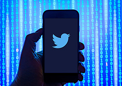 Person holding smart phone with Twitter    logo displayed on the screen. EDITORIAL USE ONLY