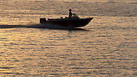 Small motorboat navigates the ocean at full speed during sunset in the caribbean