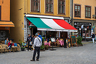 Stockholm, Sweden -- July 16, 2019.  An outdoor Italian restaurant with a colorful awning sits between a Wooden Horse Museum and a Swedish cafe in Old Town.