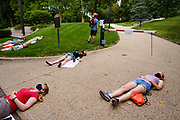 "30 JULY 2020 - DES MOINES, IOWA: People lay in front of the pedestrian gate to Governor's Mansion during a ""die in."" About 45 high school students from across Des Moines marched from downtown to the Governor's Mansion to protest Iowa Governor Kim Reynolds' proclamation ordering Iowa schools to reopen to in person classes despite the COVID-19 pandemic. The students stood in front of the mansion and chanted before staging a ""die  in"" in the street. The Governor's order mandates in person instruction rather than on line or a mix of on line and in person. Several school districts have indicated that they will disregard the Governor's orders and reopen with a hybrid system or mostly on line. The Governor will allow districts to apply for a waiver if the Coronavirus (SARS-CoV-2) infection rate is more than 15% in their community.     PHOTO BY JACK KURTZ"