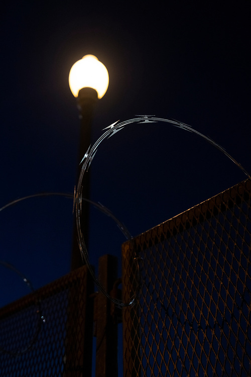 Washington DC, USA - January 19, 2021: Night falls on Capitol Hill, where recently constructed fencing topped with razor wire wraps around the U.S. Capitol Building and congressional office buildings in the wake of the January 6 attack on the Capitol.