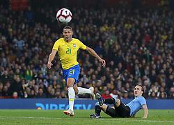 Brazil's Richarlison (left) and Uruguay's Diego Laxalt battle for the ball